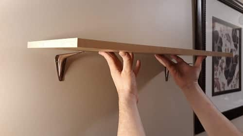 Two hands putting up a shelf on the wall.